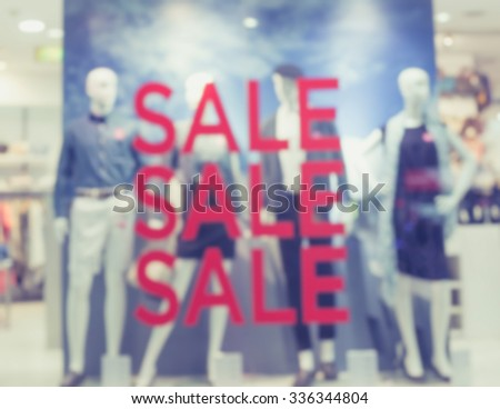 """De focused/Blur image of boutique window with dressed mannequins. Boutique display window with mannequins in fashionable dresses. """"Sale"""" signs on boutique display window. Toned image. - stock photo"""