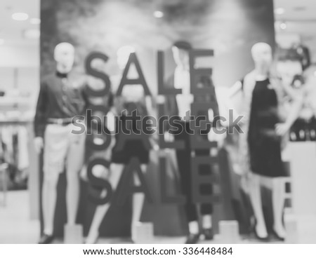 """De focused/Blur image of boutique window with dressed mannequins. Boutique display window with mannequins in fashionable dresses. Words """"sale"""" on boutique display window. Black and white image. - stock photo"""