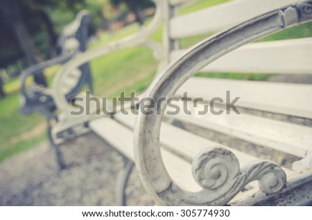 De focused/Blurred, closeup image of a white bench in a park. Beautiful curve of bench armrest in foreground. Vintage effect. - stock photo