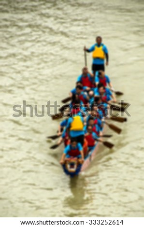 De focused/Blurred image of a dragon boat team at race. - stock photo