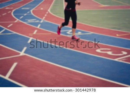 De focused/blurred image of a female runner on running track with numbers from 1 to 3.
