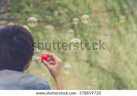 De focused/Blurred image of a girl blowing bubbles. Toned image.