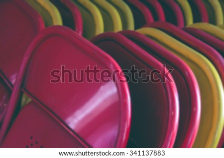 De focused/Blurred image of a row of red and yellow chairs. Vintage effect.