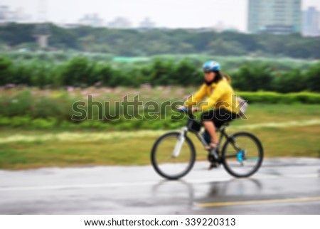 De focused/ Blurred image of a woman wearing yellow coat riding in a rainy day