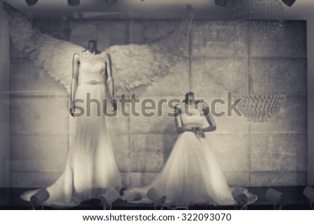 De focused/Blurred image of bridal shop display window. One mannequin dresses as an angel. Shop window with wedding dresses on mannequins. Toned image. - stock photo