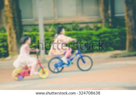 De focused/Blurred image of two little girls riding bicycles. Toned image. - stock photo