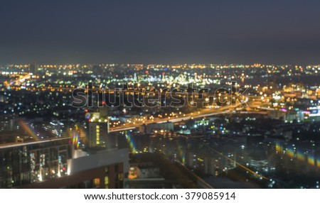 De-focused bokeh light, aerial view dark nigh twilight of Bangkok express way near logistic port