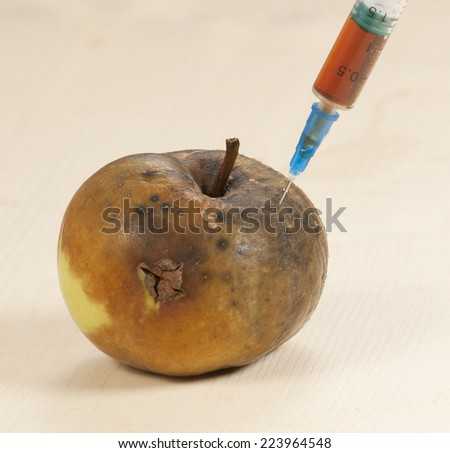"Dead apple with syringe - concept ""Narcotic drugs kill"" - stock photo"