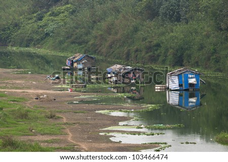 Dead arm of river houses a few boats used as poor living shelters. - stock photo