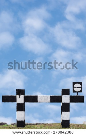 Dead end no through train railroad traffic sign isolated old grungy railway stop signal signage black white striped retro barrier closeup blue bright vertical cloudscape background summer sky clouds - stock photo