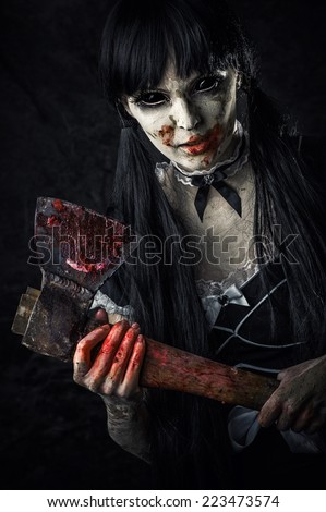Dead female zombie with bloody axe. Halloween horror. Evil ghost with black eyes - stock photo