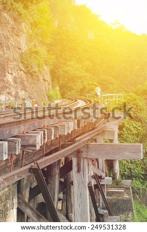Dead railway beside cliff, along Kwai river in Thailand made with vintage filter - stock photo