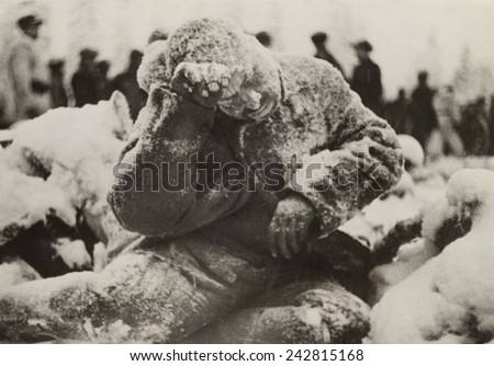 Dead Russian soldier sitting, covered with a dusting of snow, a casualty of the Battle of Suomussalmi, during the Russo-Finnish War of 1939-40. - stock photo