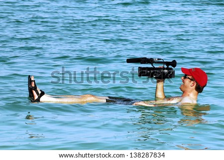 DEAD SEA, ISR - SEP 27:Cameraman filming while floating on September 17 2008.The Dead Sea is second saltiest body of water in the world, with a salt content of 33% that creates a natural buoyancy. - stock photo