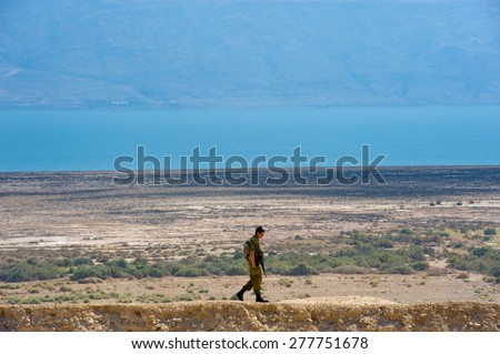 DEAD SEA, ISRAEL - OCT 15, 2014: Israeli  soldier walking alone on a hill in front of the dead sea in Israel close to Qumran - stock photo