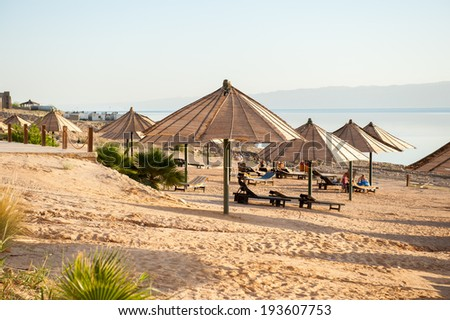 DEAD SEA RESORT, JORDAN - APR 30, 2014: Beach at the Dead Sea coast in Jordan. Dead Sea water is used for medical purposes for the people with skin problems