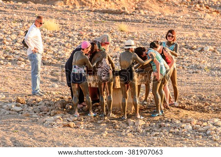 DEAD SEA RESORT, JORDAN - APR 30, 2014: Unidentified Chinese tourists in the mud of the Dead Sea. Dead Sea mud posesses the medical qualities and helps to the people with skin problems