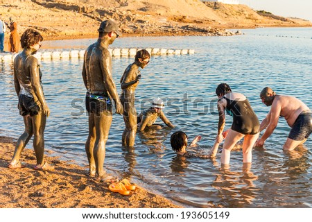 DEAD SEA RESORT, JORDAN - APR 30, 2014: Unidentified Chinese tourists pose in the mud of the Dead Sea. Dead Sea mud posesses the medical qualities and helps to the people with skin problems