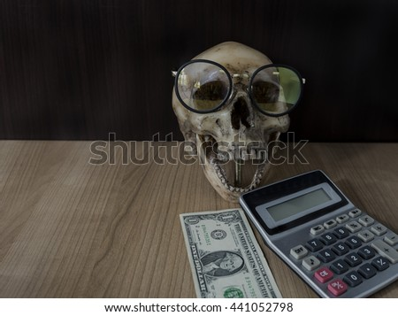 Dead skull eating bank note money with calculator,corruption money concept,drug money,money laundering,death business man money,death politician money eater,cheating money,gambling ghost money - stock photo