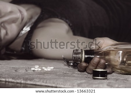 dead woman lying on the floor, bottle of whisky in her hand and pills - stock photo