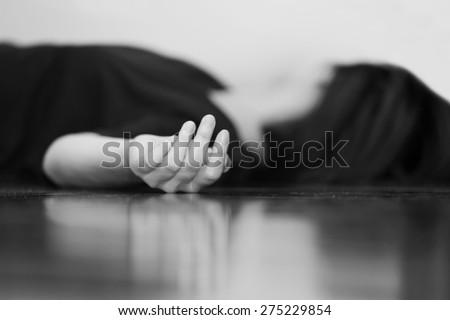 dead woman's body lying on the floor focus on hand - stock photo