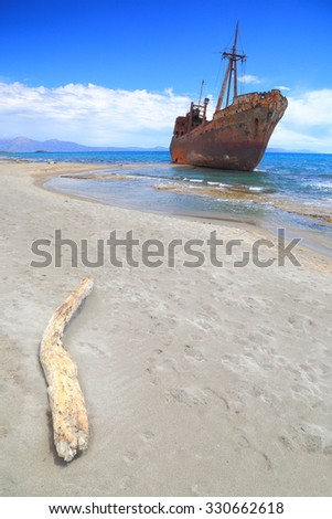Dead wood on sandy beach and old ship wreck, Gythio, Greece - stock photo