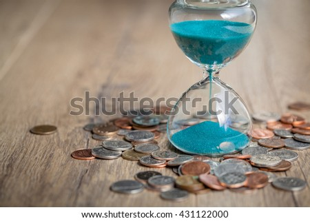 Deadline and time is money concept with hourglass and US coins currency. sandglass. - stock photo