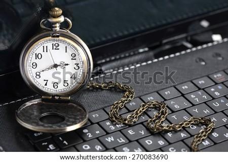 Deadline concept. Vintage pocket watch on black laptop keyboard - stock photo