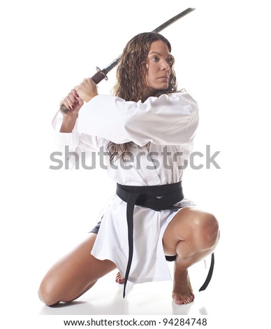 Deadly female martial artist kneeling with sword - stock photo