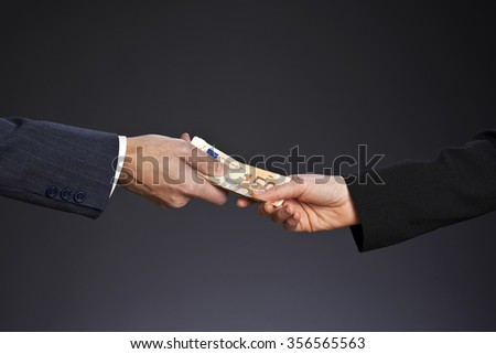 Deal! Businessman paying money  (fifty euros) to businesswoman. Woman and man hand on a gray background.