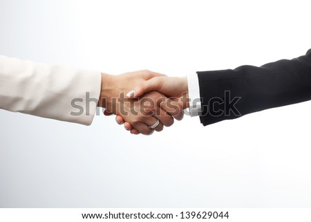 Deal! Close-up of two businesswomen shaking hands against a white backgrounds. Focus on hands