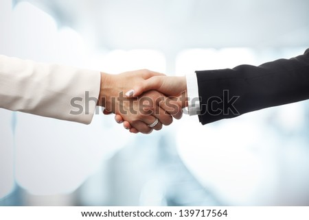 Deal! Close-up of two businesswomen shaking hands against an office backgrounds. Focus on hands