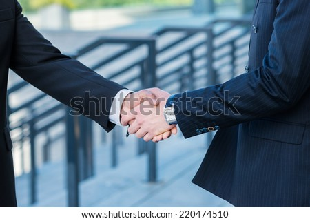 Deal confirm. Businessmen shaking hands confidently outdoors. - stock photo