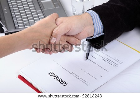 Deal. Handshake of business man and woman. Contract document in background
