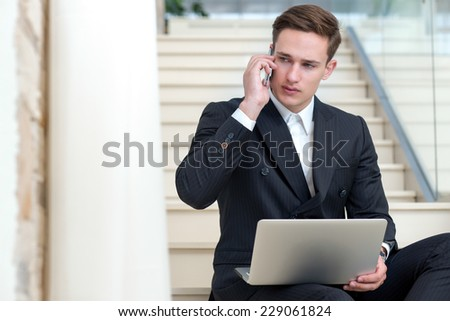 Deal on the mobile phone. Motivated and successful businessman is working with mobile phone while sitting with laptop - stock photo