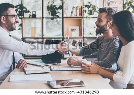 Deal! Side view of cheerful young man sitting close to his wife and shaking hand to man sitting in front of him at the desk  - stock photo