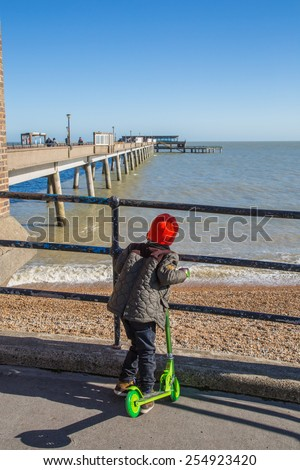 DEAL, UK - FEB 17, 2015: A child on a scooter enjoys a view of Deal pier. It is the third and only surviving pier in Deal, it opened on 19 November 1957. - stock photo