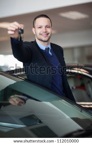 Dealer holding car keys in a dealership - stock photo