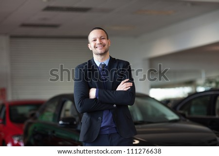 Dealer standing in front of a car in a garage - stock photo