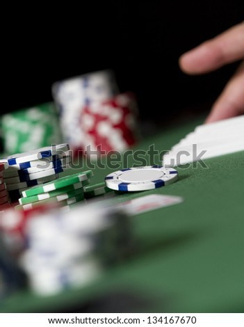 Dealing Poker Scene. a hand grabs for some cards in the distance of a poker table scene. low angle - stock photo