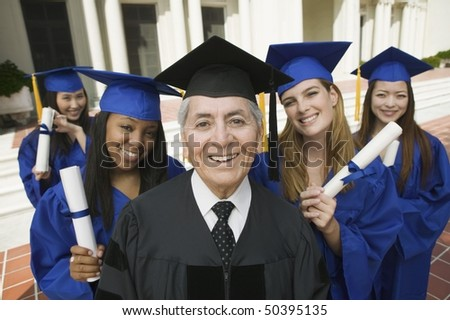 Dean and graduates outside university, elevated view, portrait - stock photo