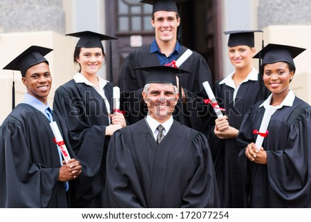dean standing with group of happy graduates outside university - stock photo