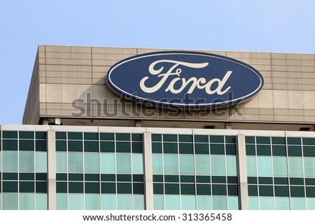 """DEARBORN, MI-AUGUST, 2015:  Sign atop the Ford Motor Company world headquarters, also known as the """"Glass House"""".  Ford operates in over 150 countries around the world. - stock photo"""