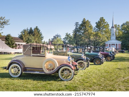 DEARBORN, MI/USA - SEPTEMBER 7, 2014: Eight antique cars, inc. a 1928 Ford Model A , and the Martha-Mary Chapel, at the Greenfield Village Old Car Festival. The Village was developed by Henry Ford. - stock photo