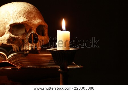Death concept. Human skull on old books near candle on dark background - stock photo