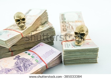 Death for money : 2 skulls with stack of 500, 1000 bath Thai money - BankNotes isolated on white background   - stock photo