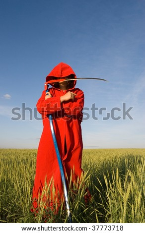 Death-like figure with scythe in the green field - stock photo