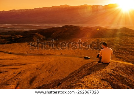 Death Valley Private Vista. Young Tourist on the Sandy Hill Enjoying the Sunset. Death Valley, California, United States. - stock photo