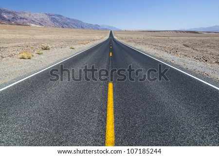 Death Valley road straight across the desert to the mountains in the distance - stock photo