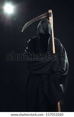 death with scythe standing in the dark - stock photo